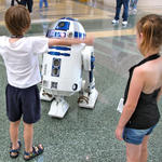 The kids play with Artoo